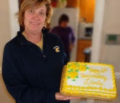 Janetta Baker with Liberty Assisted Living's 6th anniversary cake